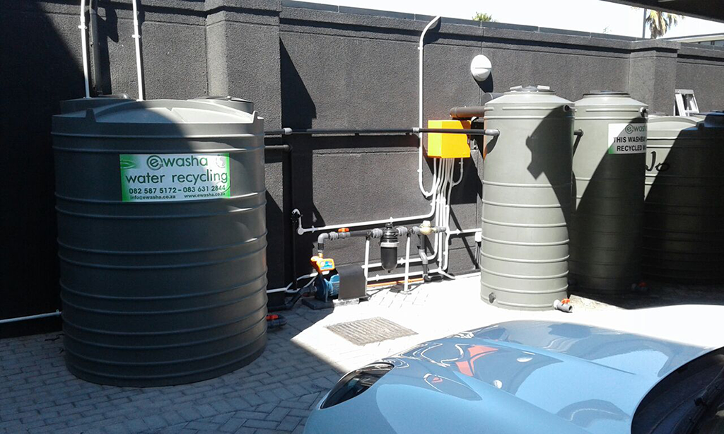 Four water tanks infront of a wall. One water tank has a sing Ewash on it. It has pipes coming out of it. The pipes run to the other three tanks.