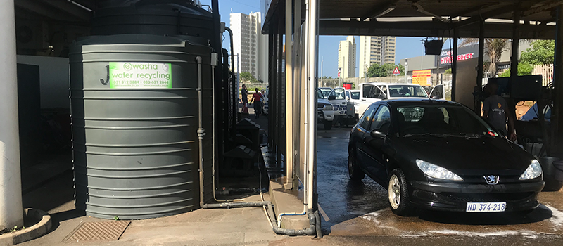 Image of a car wash, with a jojo tank on one side and a black car on the other.
