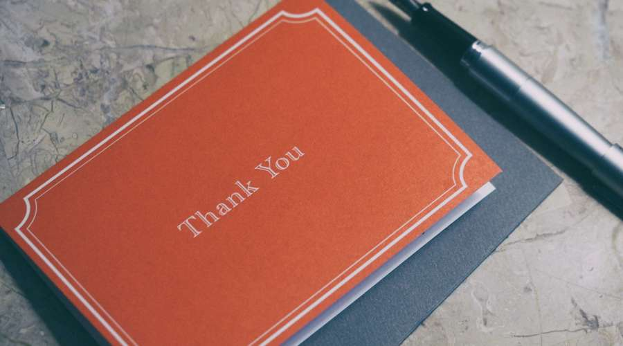 a card with word thank you on it, placed on table with a silver pen next to it.